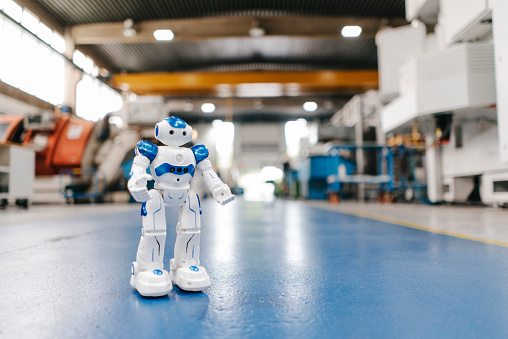 Thinking Outside The Box「Toy robot standing on floor of factory workshop」:スマホ壁紙(6)