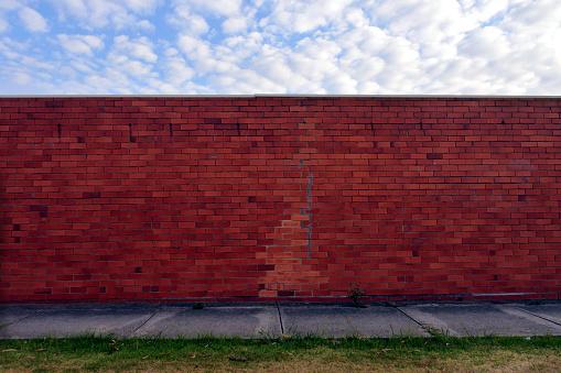 Greed「Brick wall under a cloudy sky in urban city sidewalk」:スマホ壁紙(6)