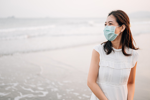 Only Women「Cheerful Asian women enjoy sunrise she walking on tropical beach sea enjoy sunrise smiling behind the facemask protective during covid-19 beach sea no people」:スマホ壁紙(0)