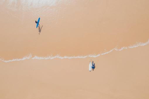 白人「Portugal, Algarve, Sagres, Praia da Mareta, aerial view of two men with surfboards at the sea」:スマホ壁紙(2)