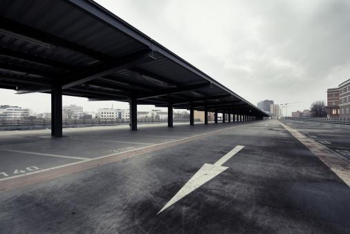 Garage「Empty Parking Spaces Against Overcast Sky」:スマホ壁紙(2)