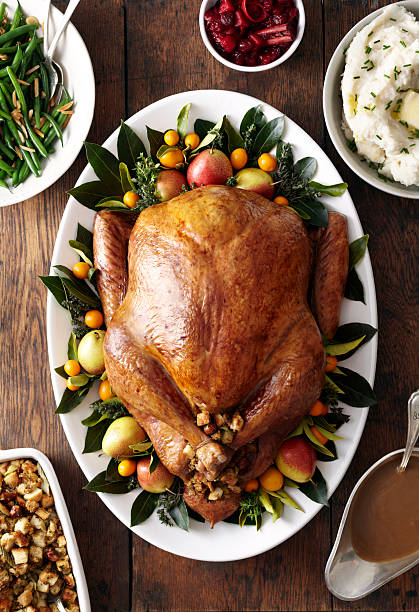 Turkey, stuffing, and gravy dishes on wood surface:スマホ壁紙(壁紙.com)