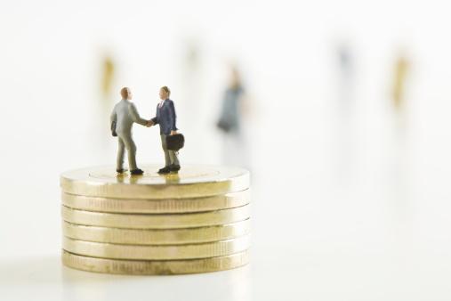 Well-dressed「Businessmen figurines shaking hands on stacks of golden coins. (Focus on foreground)」:スマホ壁紙(7)