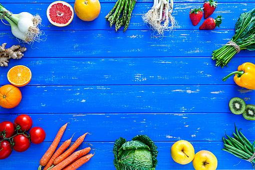 Kiwi「Fruits and vegetables border on blue table. Copy space.」:スマホ壁紙(2)