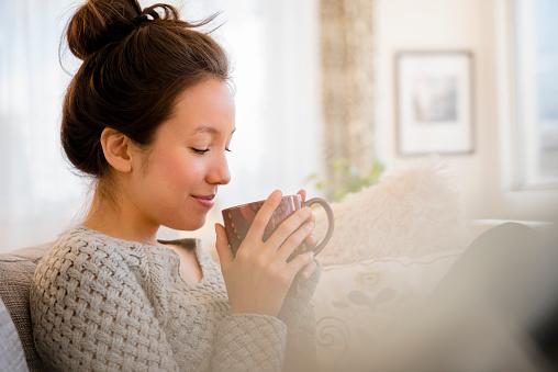 Serene People「Mixed race woman drinking coffee on sofa」:スマホ壁紙(11)