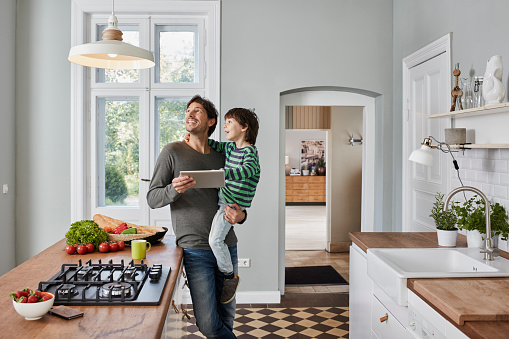 白人「Father and son using tablet in kitchen looking at ceiling lamp」:スマホ壁紙(1)