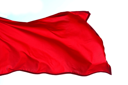 Wind「Close-up of red flag waving on white background」:スマホ壁紙(0)
