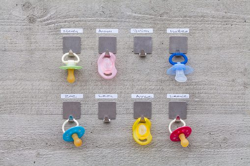 Identity「Pacifiers hanging on concrete wall with name tags」:スマホ壁紙(9)
