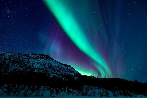 Geomagnetic Storm「Northern Lights or Aurora borealis in Lofoten islands, Norway. Polar lights in a starry sky over a snowy winter landscape」:スマホ壁紙(10)