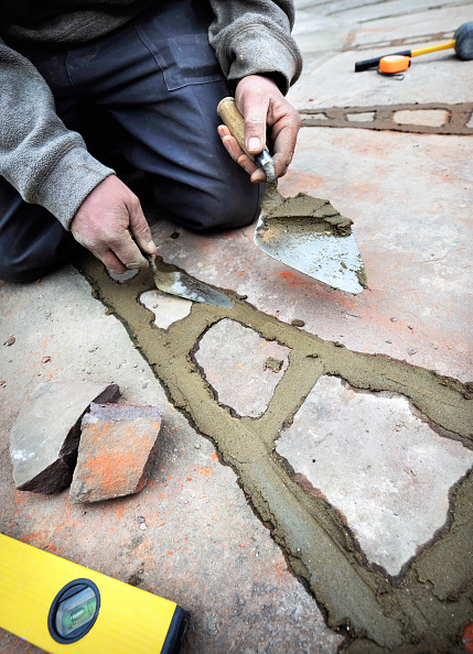 Construction Industry「Man pointing patio with natural stone slabs, UK」:写真・画像(7)[壁紙.com]