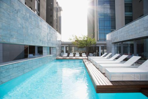 Poolside「Modern lounge chairs next to swimming pool」:スマホ壁紙(8)