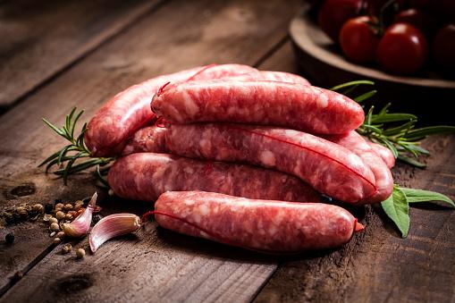Sausage「Sausages heap on dark wood table」:スマホ壁紙(1)