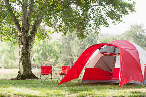 Camping「Lawn chairs and tent at campsite」:スマホ壁紙(7)