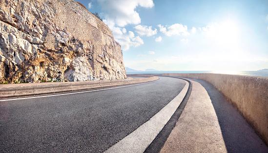 France「Empty curved coastal road on sunny day」:スマホ壁紙(9)