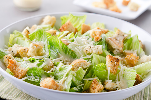 Crouton「A bowl of Caesar Salad with croutons and cheese on table」:スマホ壁紙(6)