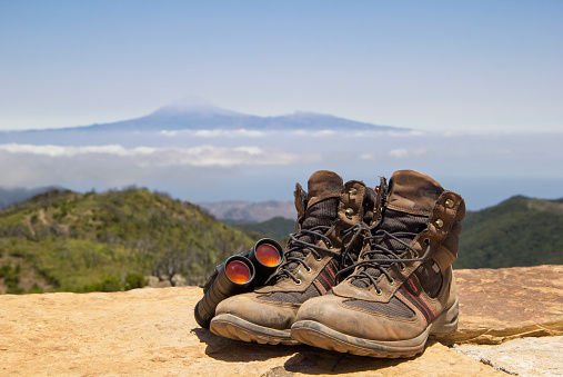 Volcano Islands「Spain, Canary Islands, La Gomera, Binoculars and pair of brown hiking boots lying at summit of Garajonay with Teide volcano looming in distant background」:スマホ壁紙(4)