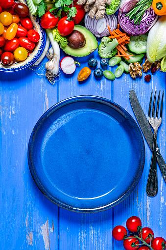 Nut - Food「Vegan food: empty blue plate and healthy fresh vegetables border. Copy space」:スマホ壁紙(14)