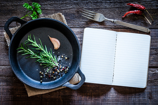 Recipe「Cookbook and cast iron pan with some herbs on wooden table」:スマホ壁紙(18)