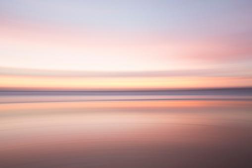 Leaving「Defocused view of ocean waves on beach under sunset sky」:スマホ壁紙(5)