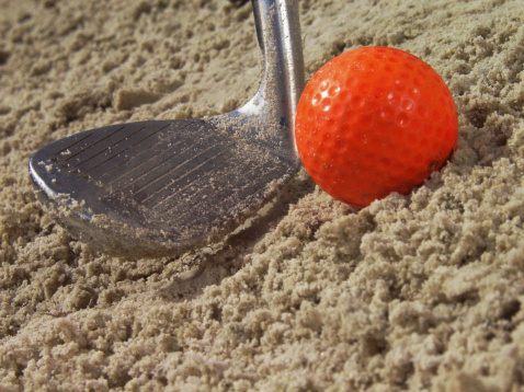 Sand Trap「Water drops on orange golf ball in sand with putter, extreme close-up」:スマホ壁紙(7)