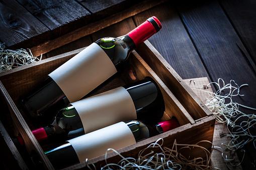 Wine Bottle「Wine bottles packed in a wooden box shot rustic wooden table」:スマホ壁紙(9)