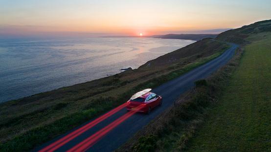 Driving「Car driving along coastal road at sunset」:スマホ壁紙(9)
