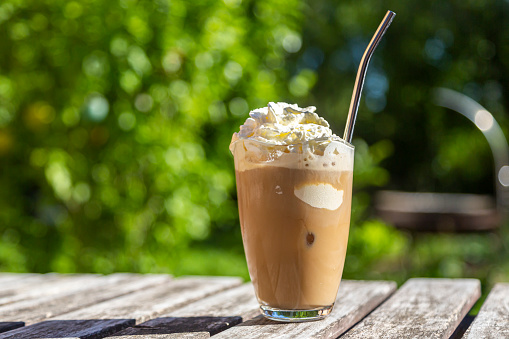 Whipped Cream「Glass of iced coffee with cream topping on garden table」:スマホ壁紙(7)