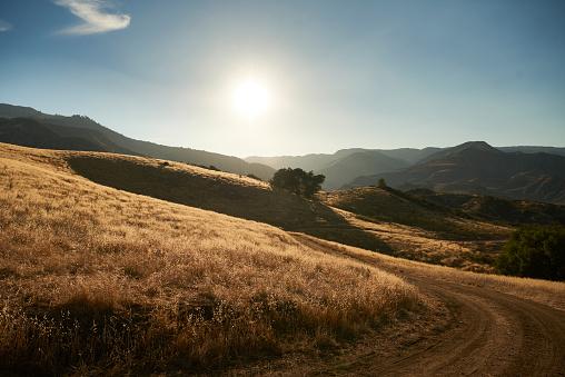 Dirt Road「Sun setting behind grassy hill」:スマホ壁紙(11)