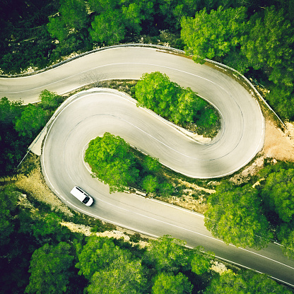 Hairpin Curve「Aerial view of a two lane winding road in a forest with a white car.」:スマホ壁紙(1)