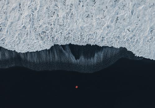 自然の景観「アイスランドの黒砂のビーチで女性の航空写真」:スマホ壁紙(6)