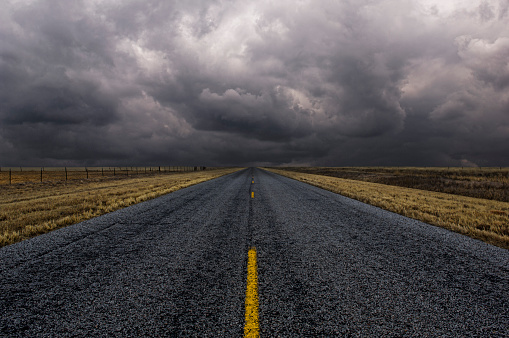 Uncertainty「Paved road under cloudy sky in remote landscape」:スマホ壁紙(0)