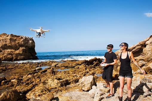 白人「young man and woman flying a personal drone」:スマホ壁紙(9)