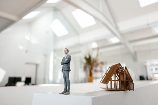 Businessman「Businessman figurine standing on desk next to architectural model」:スマホ壁紙(3)