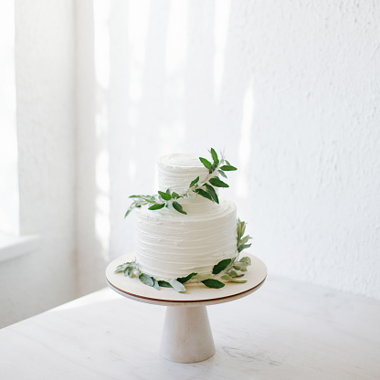 Dessert「Two tiered wedding cake with icing and olive branch decoration」:スマホ壁紙(1)