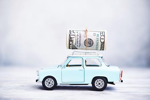 Insurance「Little blue car with cash roll on roof rack」:スマホ壁紙(1)