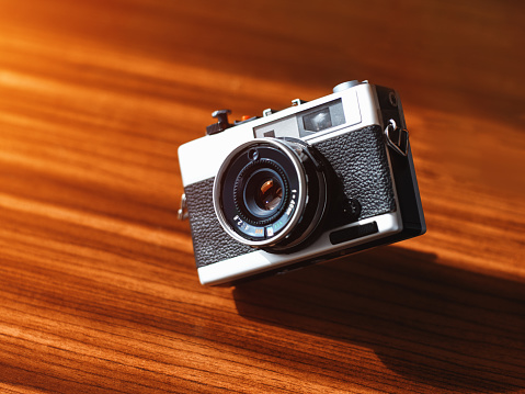 1980-1989「Rangefinder film camera floating in the air with a wooden table at the backtround」:スマホ壁紙(5)