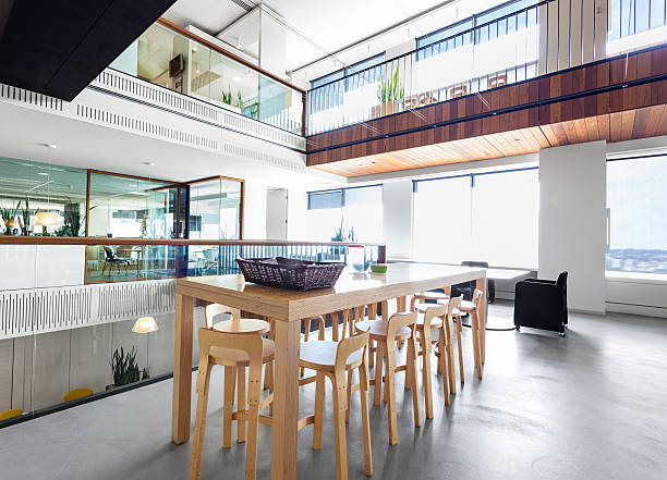 Modern, high wooden table in a large office space:スマホ壁紙(壁紙.com)