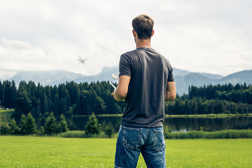 1人「Germany, Bavaria, Pfronten, young man flying his drone at lakeside」:スマホ壁紙(2)