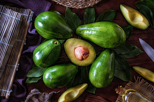Avocado「Avocado fruits and sliced avocados on a wooden table」:スマホ壁紙(3)