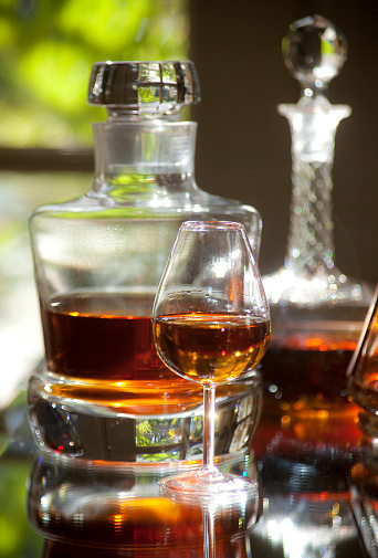 Bar - Drink Establishment「Small snifter of brandy or whiskey and a crystal decanter behind it in a elegant home bar or drink establishment—part of a series」:スマホ壁紙(5)