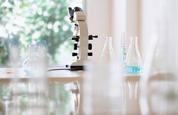Microscope and beakers in laboratory:スマホ壁紙(壁紙.com)