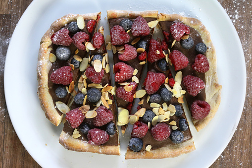 Crunchy「Image of homemade chocolate pizza tart with fresh raspberries, blueberries, almond and icing sugar, baked pizza crust filled with hazelnut chocolate spread and topped with berry forest fruit, raspberry, strawberry berries, sliced eaten as gourmet dessert」:スマホ壁紙(1)