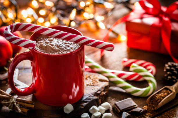 Homemade hot chocolate mug with red and white candy cane on rustic wooden Christmas table:スマホ壁紙(壁紙.com)