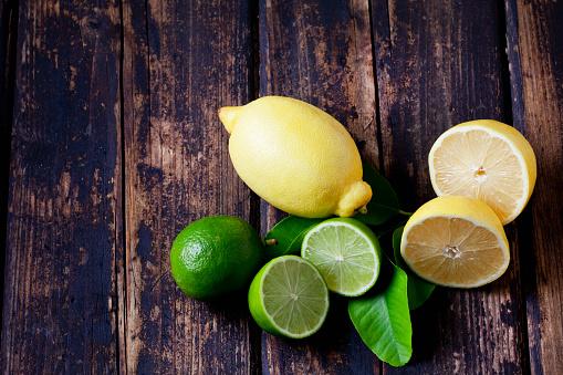 Tasting「Whole and sliced lemons and limes on dark wood」:スマホ壁紙(7)