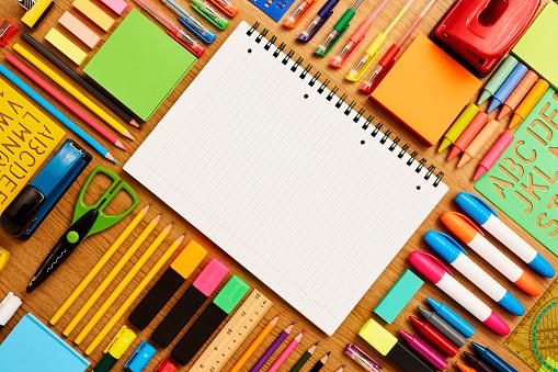 斜めから見た図「Spiral note pad surrounded by school supplies on table」:スマホ壁紙(10)
