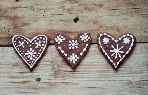 Gingerbread Cookie「Three gingerbread hearts decorated with sugar icing on wooden table」:スマホ壁紙(4)