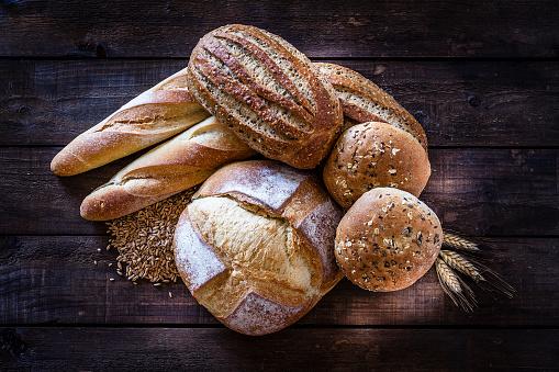 Sourdough Bread「Loaves of bread heap shot on rustic wooden table」:スマホ壁紙(2)