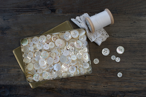 Sewing「Metal box of different old mother-of-pearl buttons on dark wood」:スマホ壁紙(11)