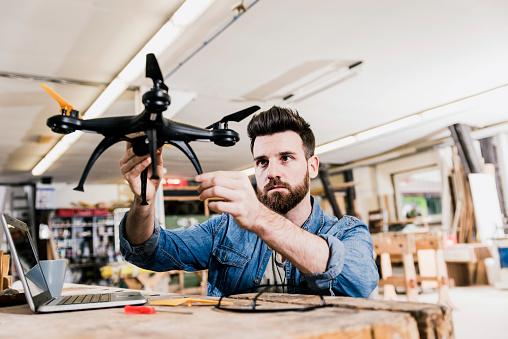 白人「Man working on drone in workshop」:スマホ壁紙(7)