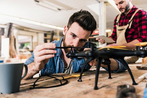 日曜大工「Man working on drone in workshop」:スマホ壁紙(10)